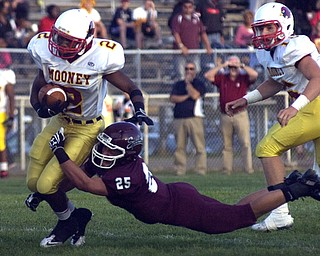 Kelli Cardinal/The Vindicator.Cardinal Mooney running back C.J. Arnill tries to avoid the tackle Friday night against Boardman defender Mario Graziani at Boardman.