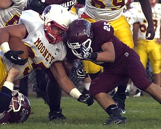 Kelli Cardinal/The Vindicator.Cardinal Mooney fullback Anthony Dermotta comes head to head Friday night against Boardman defender Mario Graziani at Boardman.