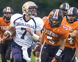Kelli Cardinal/The Vindicator .Lowellville junior Phil Ginnis carries the ball Friday night against Springfield's Jake Ohlin, center, and other defenders at Springfield High School.