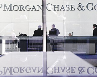 People stand in the lobby of JPMorgan Chase headquarters in New York. The bank will pay $920 million and must admit that it failed to oversee trading that led to a $6 billion loss.