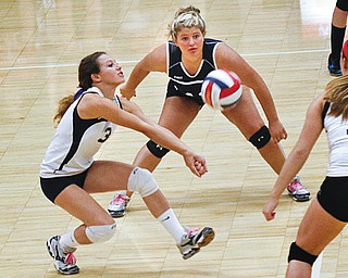 Fitch's Cali Mikovich (3) digs the ball while Alex Corradi (43) and Sydney Greenwood (17) watch Thursday night.