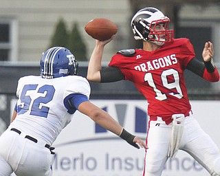 William D. Leiws The Vindicator  Niles QB Kyle Paden(19) gets off a first QTR pass as Poland's Mike Audi (52) persues at Niles 9-20-13.