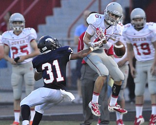 Fitch #31 Tyler Hewlett pokes the ball out of the hands of Dover receiver #6 Cory Contini on a deep pass late int he 1st quarter.