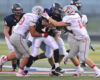 Fitch quarterback #18 Antwan Harris runs the ball while Dover #18 Dillon Stephens and #11 Alex Bowman attempt to bring him to the ground.
