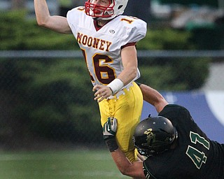 Youngstown Cardinal Mooney quarterback Jon Saadey throws a completed pass while in the grasp of  St. Vincent - St. Mary's Aaron Adkins  in the first  quarter of a high school football game at St. Vincent - St. Mary High School on Friday, Sept. 20, 2013, in Akron, Ohio. (Michael Chritton/Akron Beacon Journal)