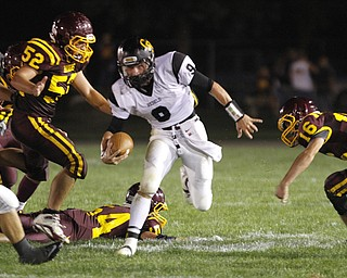 .          ROBERT  K. YOSAY | THE VINDICATOR..BIG HOLE as Crestviews #9 Collin Gilber QB goes through a big whole as #52 South Range Zach Baird  #54 (on ground) Ben Baird and#16  Zach Thorpe can only watch as he scampers for a first down during second quarter action..Crestview @ South Range in North Lima