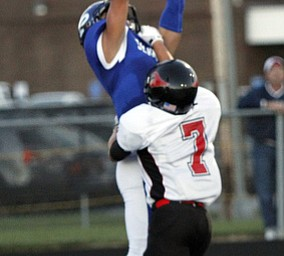 .          ROBERT  K. YOSAY | THE VINDICATOR..Polands #8  George Chammas  Jumps up for the a touchdown as #7 Nick Luchansky from Canfield trys  to defend..Canfield at Poland