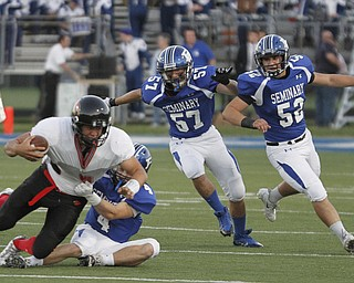 .          ROBERT  K. YOSAY | THE VINDICATOR..Canfield #9 Kimu Kim is pulled down by #4 Poland  Dylan Garver as #57  Colin Rody and#52  Mike Audi look on.. he was stopped for a loss in first quarter action..Canfield at Poland