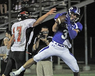 .          ROBERT  K. YOSAY | THE VINDICATOR..Polands #3  Tyler Evan pulls in a second quarter pass as Canfields  #17 Aaron Jenkins tries to defend..Canfield at Poland