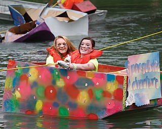 """Jenna Wymer and Gabbie Carr pull past a sunken boat in their """"SpongeBob Adventure"""" boat. The Raider Regatta takes place at the lake behind the old high school at Memorial Park. Sophomores build a cardboard boat with a theme and make a lap across the lake and back."""