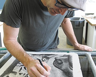 Using granite limestone as his canvas, YSU student Christopher Bosi sketches a drawing for a lithograph.