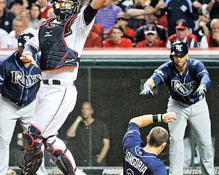 Indians catcher Yan Gomes leaps for the high throw as the Rays' Evan Longoria (3) slides into home to score on a two-run double by Desmond Jennings during the fourth inning of the AL wild-card playoff game Wednesday at Progressive Field in Cleveland. The Rays eliminated the Indians from post-season play with a xx-xx win.