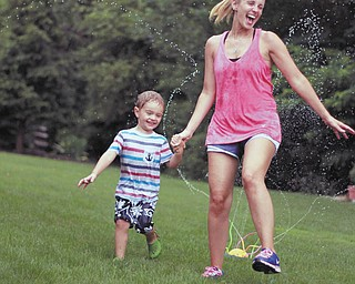 Three-year-old Sam Manning and his mommy, Samantha Manning, are having fun in the sprinkler on a hot day. Sent by grandmother of Sam, Joyce Buzzacco.