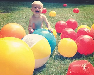 Finnegan Gable is surrounded by balloons at his first birthday party.