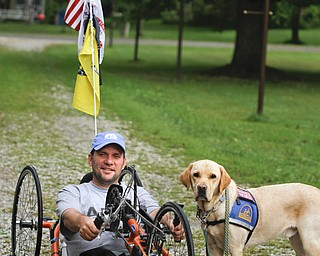 MADELYN P. HASTINGS | THE VINDICATOR..Brett Clingan of Champion has a neurological disorder but is still competing in the Peace Race using a hand cycle and the help of his Labrador Golden Retriever, Albus.... - -30-..