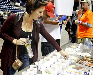 MADELYN P. HASTINGS | THE VINDICATOR..Chelsea Mayer of North Canton tastes raw hops at the PumpHouse Homebrew Shop booth set up at the Beer Fest at the Covelli Center on Saturday, October 5, 2013. The company based out of Struthers offered several types of brewing products for guests to taste.... - -30-..