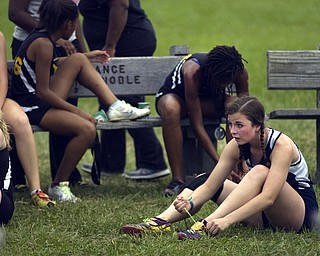 Kelli Cardinal/The Vindicator .Stephanie Waltman, a junior from Austintown Fitch, rests and ties her shoe Saturday after competing in the boys and girls Division I open race during the Legends Cross Country Meet at Trumbull County Fairgrounds.