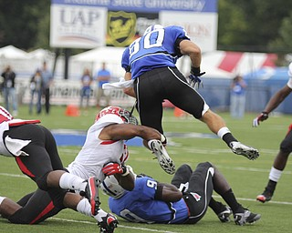 Youngstown State's Teven Williams wraps up the leg of Indiana State's Tanner Riley (80) during the first quarter of Saturday's matchup at Indiana State. Dustin Livesay  |  The Vindicator  10/05/13  Indiana State University, Terre Haute, Indiana.