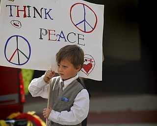 "MADELYN P. HASTINGS | THE VINDICATOR..Chase Britton, 6, of Youngstown holds a sign that reads ""Think Peace"" in the third annual nonviolence parade to kick off nonviolence week in downtown Youngstown on Sunday, October 6, 2013.... - -30-.."