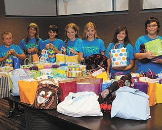 """SPECIAL TO THE VINDICATOR Noah McLemore, an eighth-grader from Canfield whose aunt was diagnosed with pancreatic cancer, looked for ideas to help her feel better. He and his mother put together a package he calls a """"cancer care bag."""" For three months he and other middle school students collected donations of items and prepared the bags. The bags each contain a water bottle, lip balm, mints, a lap blanket and a journal. They delivered 108 bags to the Joanie Abdu Comprehensive Breast Care Center, and two bags were given to people the children know, who are suffering with cancer. Above, middle school students participating, from left, are Noah Clark and Emily Hura of Columbiana; Elijah McLemore of Canfield, Savannah Pew of Greenford, Natasha Flak of Salem, Cheyenne Trump of New Waterford and Noah McLemore."""