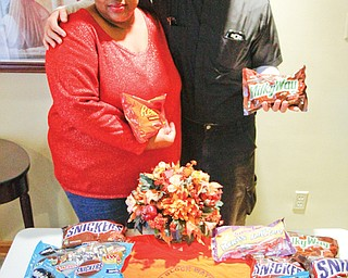 Victoria Allen, president of ICU Block Watch, and the Rev. Greg Maturi, pastor of St. Dominic Church in Youngstown, show some of the candy being collected for distribution at the Neighborhood Harvest. The event is planned from 3 to 5 p.m. Sunday in the gated lot at the corner of Cottage Grove and Auburndale Avenue in Youngstown.