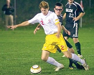 Cardinal Mooney's Clayton Walker fights to stay in control of the ball against Salem defender Mike Anzevino during a Division II sectional match Tuesday night. Mooney won, 6-0, and will meet Lakeview on Saturday night.