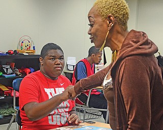 Maurice Castel, 15, fist-bumps his aunt, Bonnie Hunter of Wisconsin, after he finished a lesson at the new Potential Development High School for Autism in Youngstown. Maurice is nonverbal but has shown improvement through the Potential Development program. The non-charter public school for teens in grades nine through 12 on the autism spectrum had a ribbon-cutting Wednesday.