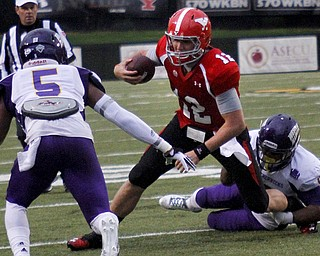 MADELYN P. HASTINGS | THE VINDICATOR..YSU's Kurt Hess (12) runs with the ball from Western Illinois' Martinez Davis (5) and Jonathon Rollins (4) during Youngstown's homecoming game on October 19, 2013.... - -30-..