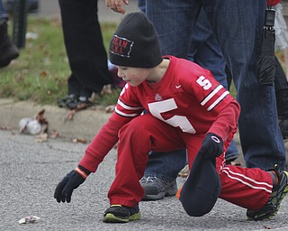 AJ Boehlke (6) of Campbell picks up candy during the Homecoming parade on Fifth Ave. in Youngstown on Saturday. Dustin Livesay  |  The Vindicator 10/19/13  Youngstown.
