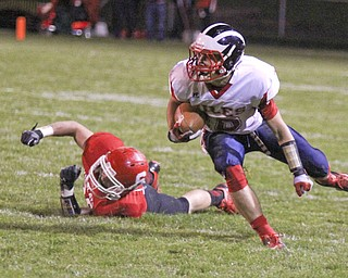 Niles McKinley's Chris Parry (10) keeps his balance after shedding a tackle by Marcus Donnadio (20) of Struthers during the first quarter of Friday nights matchup at Struthers High School.  Dustin Livesay  |  The Vindicator 10/25/13  Struthers High School.