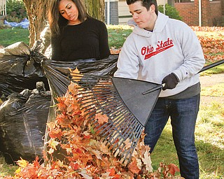 Natalia Mahdee, a Youngstown Christian School sophomore, and Perry Chickonoski, a senior, bag leaves Monday at homes in the neighborhood surrounding the school as part of a service project.