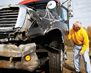 Charles Jungfleisch of Georgetown, Pa., examines a semi tractor that was for sale in a Monday surplus-vehicle auction after it had been forfeited to the Mahoning County Prosecutor's Office as restitution by a Las Vegas truck driver who rammed it into an Austintown nightclub. The highest bid for it was $6,500.