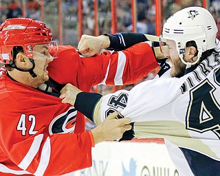 The Hurricanes' Brett Sutter and Penguins' Joe Vitale come to blows during the first period of their game Monday in Raleigh, N.C. The Penguins downed the Hurricanes, 3-1.
