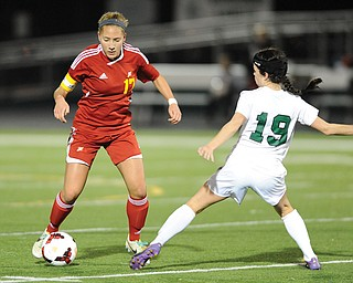 Cardinal Mooney's Juliana Vazquez (17) dribbles around Elyria Catholic defender Jenna Ellingson (19) on Tuesday night during the second half of a Division III girls soccer regional semifinal.