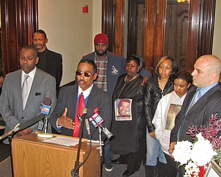 Richard Rollison III, at microphone, addressed the news media Wednesday at Warren City Hall, flanked by Mayor Doug Franklin, left, Warren Safety-Service Director Enzo Cantalamessa, right, and other Rollison family members and friends. Rollison is the father of Richard Rollison IV, 24, who was shot to death Saturday; the father joined in a plea to end further violence in the city.