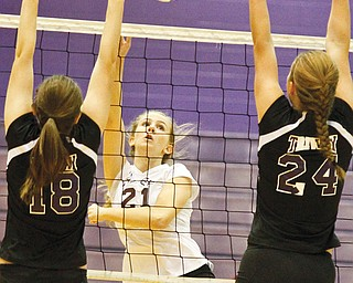South Range's Lexi Desantis hits the ball over the net as Triway's Macie Wengerd (18) and Courtnay Cruise (24) defender during a Division III regional semifinal volleyball match Wednesday at Barberton High School. The Raiders fell 3-1.