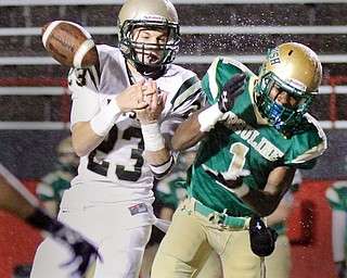 Ursuline's Ben Phillips (1) and Akron SVSM's Nathan Bischof (23) battle for a pass during the first quarter of Thursday's game at Stambaugh Stadium. SVSM won 40-7.