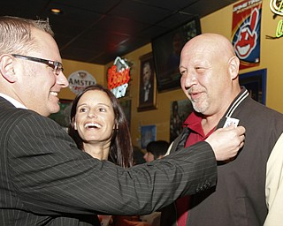 MADELYN P. HASTINGS I THE VINDICATOR..Jim Davis gives Joe Halas an election sticker while Maria Morales-Latone laughs during the election party at Jay Jay's Roadhouse on November 5, 2013.