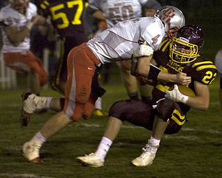Kelli Cardinal/The Vindicator .South Range running back Billy Goodall fails to avoid the tackle by Cuyahoga Heights defender Jordan Martin during the first half Friday night at Memorial Field in North Lima.