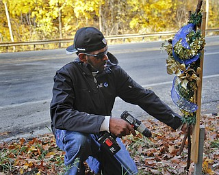 MADELYN P. HASTINGS | THE VINDICATOR..Vincent Campbell of Ferrel, PA places a decorated cross at the site of a two vehicle car accident along Connelly Blvd. near the intersection of Route 62. The accident caused three deaths with four others injured at around 10:00 p.m. on Friday, November 10, 2013.  ... - -30-..