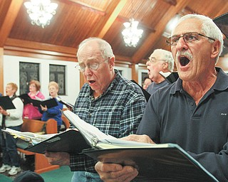 Robert Greitzer of Braceville, left, and John Viggiano of Poland give it their all during a recent rehearsal of Mahoning Valley Chorale at Good Hope Lutheran Church in Boardman. The group, formerly known as Seraphim Chorus, changed its name to better reflect its music and members.