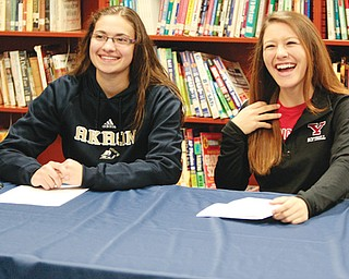 Austintown's Megan Sefcik and Cali Mikovich sign their letters-of-intent Wednesday at the Fitch High School Library. Sefcik will play basketball at Akron, and Mikovich will play softball at Youngstown State.
