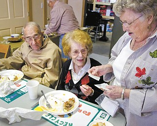 "Kelli Cardinal/The Vindicator .Betty Clayton, right, from Salem, hands out a poem called ""Pennies from Heaven"" to Marilyn Burkley, from Canfield, and her husband, Sam, during the Salem Scampers annual fish and chicken fry Sunday in North Jackson. The Burkleys joined the Scampers in 1980."