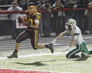 .          ROBERT  K. YOSAY | THE VINDICATOR..#30 Joe Alessi  runs out of the grasp of  #3 Mogadore   Brendon Schrock for South Range first TD on their first possesion.. South Range  .South Range and Mogadore in Minerva Ohio .....-30-