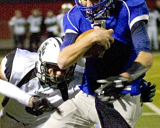 Kelli Cardinal/The Vindicator .Hubbard quarterback Brennan Wassil attempts to avoid the tackle Friday night by Aurora defender Ryan Devine at Falcon Field in Austintown.