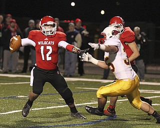 William D Lewis The Vindicator Struthers' QB Gary Muntean(12) is pursued by Mooney's  Anthony Dermotta(35) during playoff action Friday in Niles.