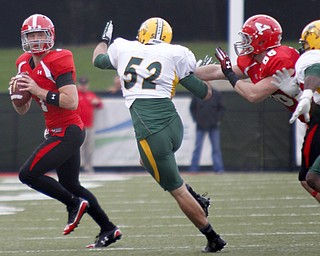 MADELYN P. HASTINGS | THE VINDICATOR..YSU's Tanner Garry (7) prepares to pass the ball while Carson Sharbaugh (86) holds back NDSU's Travis Beck (52) during their game at Stambaugh Stadium on November 16, 2013. The Penguins lost to Bisons 17-35.... - -30-..