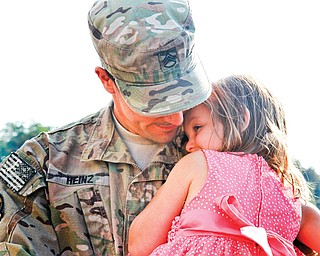 Oliva Heinz, 4, hugs her dad, Matthew Heinz, who just returned from combat after being gone for almost a year.