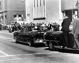 Secret servicemen standing on running boards follow the presidential limousine carrying President John F. Kennedy, right, rear seat, and first lady Jacqueline Kennedy, left, as well as Texas Gov. John Connally and his wife, Nellie, in Dallas, Texas, Nov. 22, 1963.  Moments later, President John F. Kennedy was shot by an assassin.