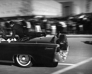 The limousine carrying mortally wounded President John F. Kennedy races toward the hospital seconds after he was shot in Dallas, Tx., Nov. 22, 1963.  With secret service agent Clinton Hill riding on the back of the car, Mrs. John Connally, wife of the Texas governor, bends over her wounded husband, and Mrs. Kennedy leans over the president. (AP Photo/Justin Newman)